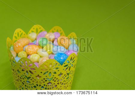 Jelly beans in a yellow metal basket on a green background
