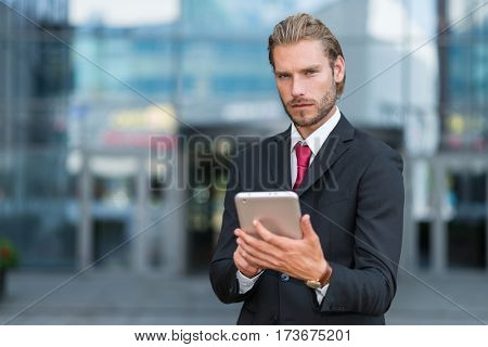 Young handsome businessman using his tablet
