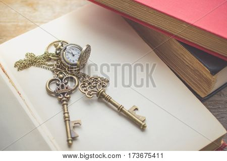 Old vintage key on stack of old book with copy space in morning light for unlock or eductaion concept