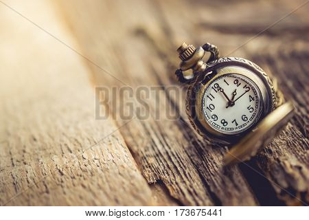 close up gold pocket watch on wooden with copy space for time history past concept