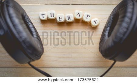 Relaxation and cozy with word therapy on wooden background and copy space for music therapy concept