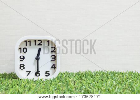 Closeup white clock for decorate show a half past twelve or 12:30 a.m. on green artificial grass floor and cream wallpaper textured background with copy space