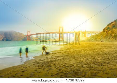 Golden Gate Bridge in Baker Beach at sunset. Tourists walking and playing with dog on popular Baker Beach. Holidays, travel and leisure in San Francisco, California, United States.