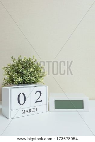 White wooden calendar with black 2 march word with clock and plant on white wood desk and cream wallpaper textured background selective focus at the calendar