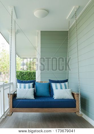 Outdoor Wooden Porch Swing Bench With Blue Pillows.