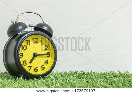 Closeup black and yellow alarm clock for decorate show a quarter past seven or 7:15 a.m. on green artificial grass floor and cream wallpaper textured background with copy space