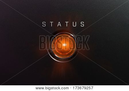 Status indicator or lamp. Orange glowing warning lamp or button black panel with the words,