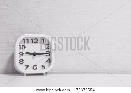 Closeup white clock for decorate show a quarter past nine or 9:15 a.m. on white wood desk and cream wallpaper textured background in black and white tone with copy space