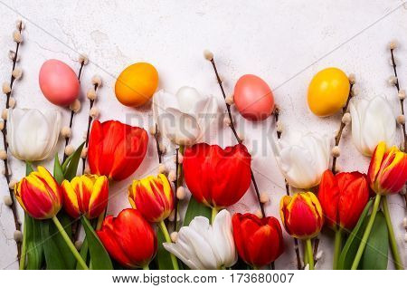 Colorful tulips with branches pussy willows and easter eggs on old background. Festive  Easter concept with copy space. Flat lay