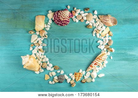 An overhead photo of sea shells and pebbles, forming a frame on a vibrant turquoise background, with a place for text inside. A design template for a summer vacation banner