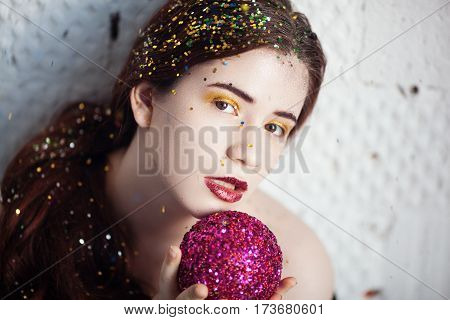 Portrait of a girl covered with spangles on a holiday