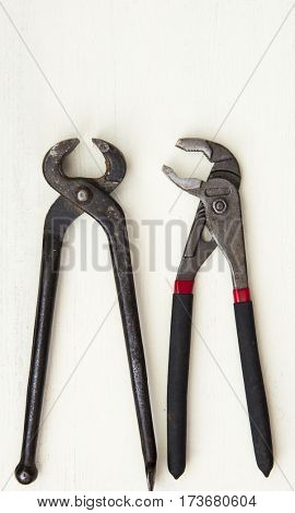 Pliers and wrench on a wooden background