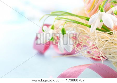 Easter background. Beautiful spring snowdrop flower with decorations on the wooden table, pastel colors, border design