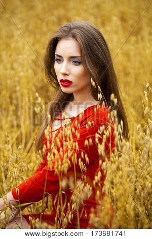 Portrait of a young brunette woman in red dress on a background of golden oats field, summer outdoors