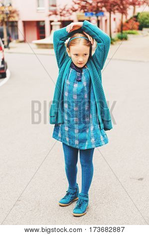 Outdoor fashion portrait of adorable little girl of 8-9 year old, wearing blue clothes and shoes