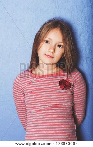 Interior portrait of cute 7-8 year old girl, wearing stripe t-shirt, leaning on the wall