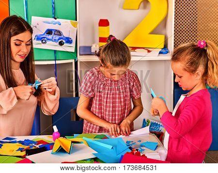 Paper craft work for children. Dreams flight of child in kindergarten. Happy boy child playing with origami airplane in kindergartener or school.