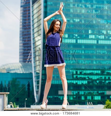Young brunette woman in a blue dress is stretching near skyscrapers