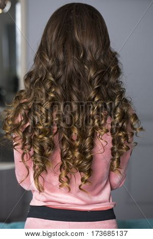 Female Long wavy brunette hair, rear view, indoor beauty salon