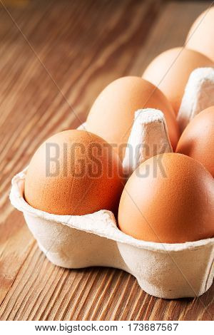 Eggs in box on a wooden background. brown eggs in a carton package