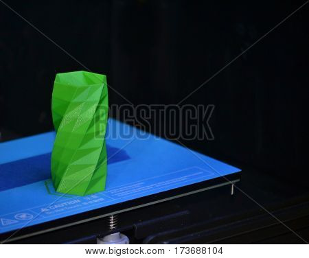 The object printed 3D printer on a blue and black background in the 3D printer. Automatic three dimensional 3d printer performs plastic green colors modeling in laboratory.