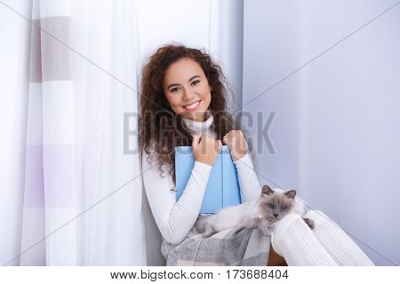 Beautiful young woman with cat on lap reading book