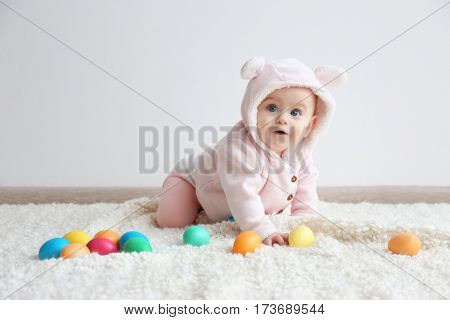 Cute funny baby with colorful Easter eggs at home