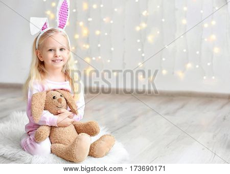 Cute funny girl with bunny ears and cuddly toy sitting on floor at home