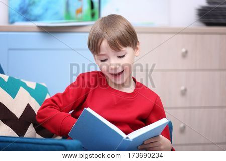 Cute little boy reading book at home
