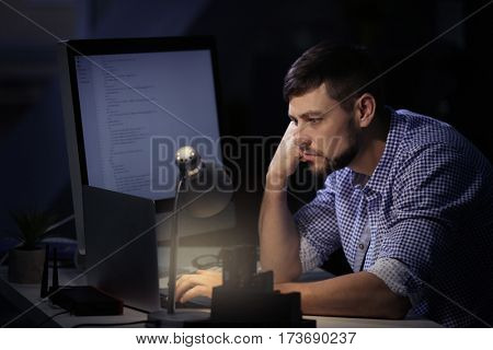 Handsome young programmer working at home late in evening