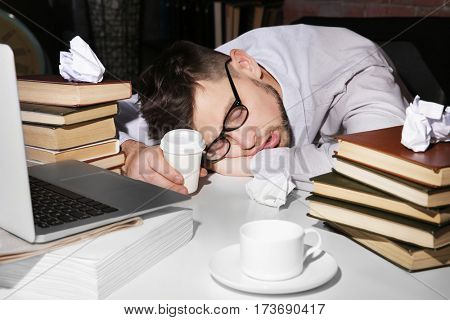 Young man fell asleep during reading at workplace