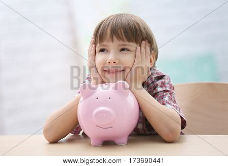 Cute little boy with piggy bank on blurred background