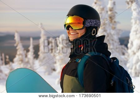 girl snowboarding in the mountains at sunset time
