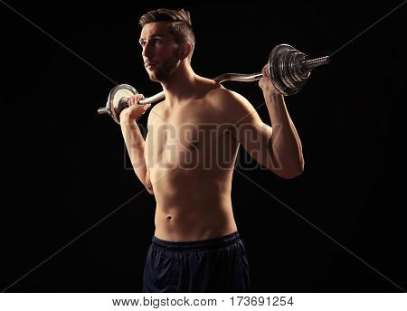 Sporty man doing exercises with barbell on black background