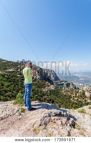 Male traveler enjoying the views from the mountains of Montserrat in Spain and makes a photo on his camera. The man in blue jeans and a yellow T-shirt on the background of the Monastery of Montserrat and nature