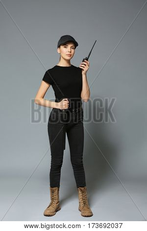Beautiful young woman in security uniform on grey background