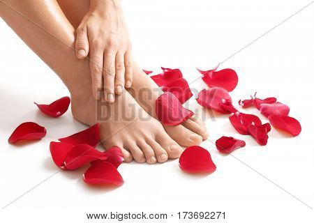Female legs, hand and red petals on white background