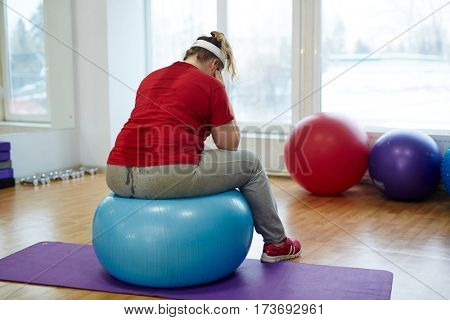 Back view portrait of sweaty overweight woman working out in fitness studio: sitting on big fitness hanging her head looking upset and exhausted
