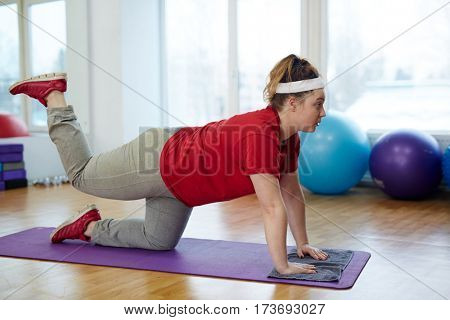 Side view portrait of tired overweight woman working out in fitness studio:  doing leg kickbacks on yoga mat