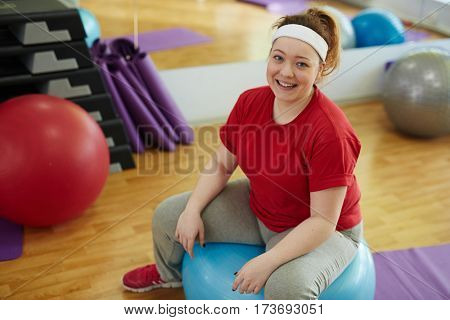 Portrait of cute plump woman working out in fitness studio: resting sitting on ball and looking at camera, smiling