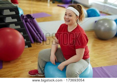 Portrait of cute obese woman working out in fitness studio: performing ball exercises, sitting on it and smiling