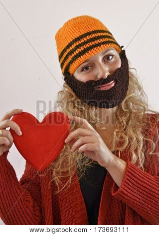 Funny blonde woman wearing beard mask and heart