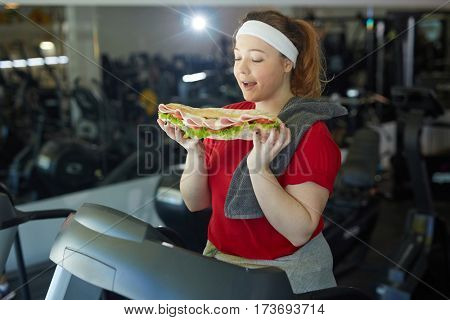 Portrait of cute fat woman licking her lips about to eat huge tasty sandwich while working out in gym