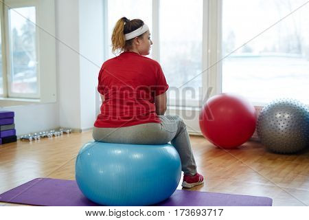 Back view portrait of overweight woman working out in fitness studio: bouncing on big fitness ball looking away