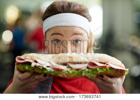 Closeup portrait of cute overweight woman holding big tasty fattening sandwich in from her face, wide-eyed and excited