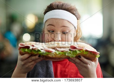 Closeup portrait of young obese woman holding big fattening sandwich in front of her face