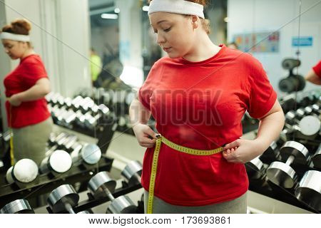 Portrait of cute obese woman standing against mirror in gym and measuring waist size with tape after workout