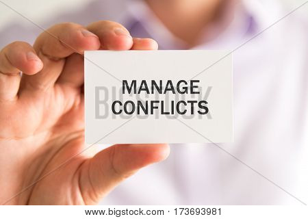 Businessman Holding A Card With Manage Conflicts Message