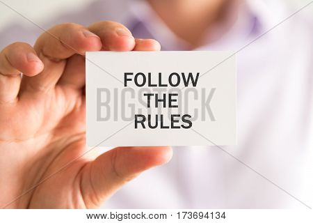 Businessman Holding A Card With Follow The Rules Message