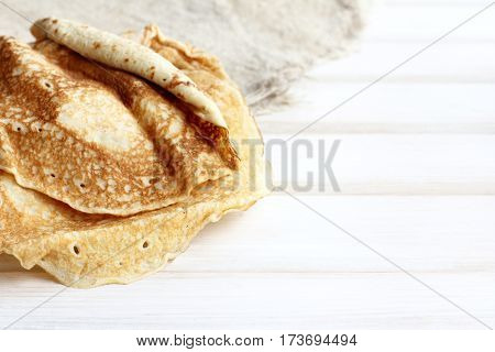 ruddy pancakes on a light wooden background table / festive Shrovetide